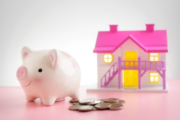 甘い家とピンクのテーブルで貯金箱の周りのコイン。家や家の節約の概念を購入するために節約
