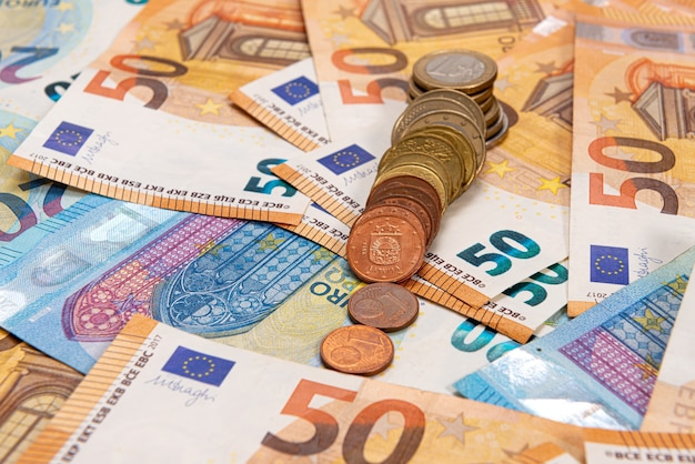 Coins on the background of euro banknotes, euro bill as part of the economic and trading system, close-up