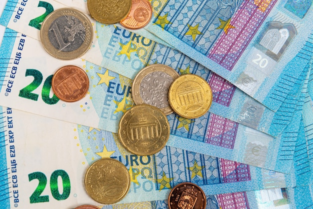 Coins on the background of twenty euro banknotes, close-up