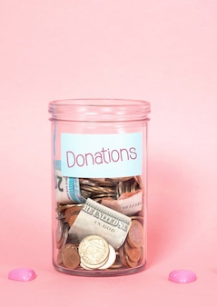 Coins and banknotes in glass money jar with label, financial donations, charity, fund rising concept.