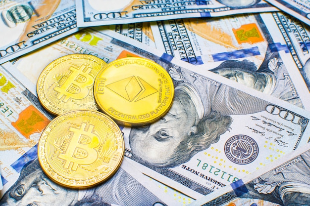 Coins bitcoin btc on background of banknotes one hundred dollars