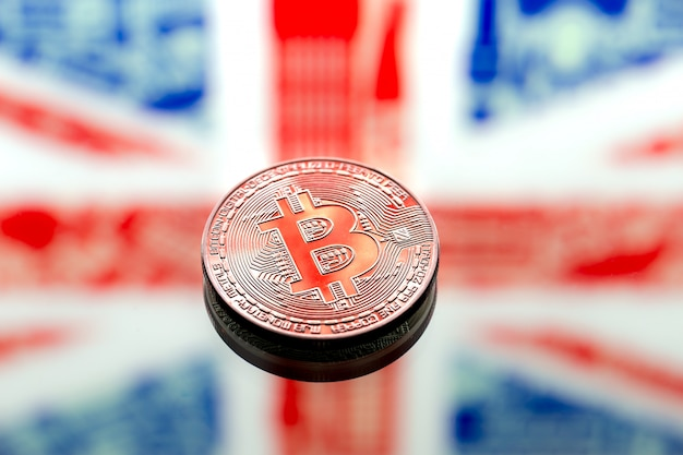 Coins bitcoin over great britain and the british flag, concept of virtual money, close-up. conceptual image.