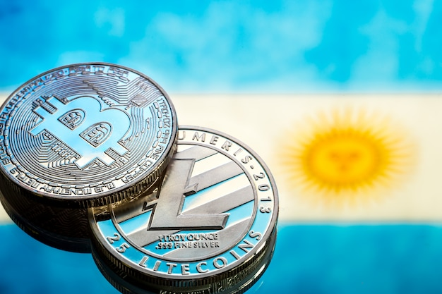 Coins bitcoin and litecoin, against the background of argentina flag, concept of virtual money, close-up. conceptual image.