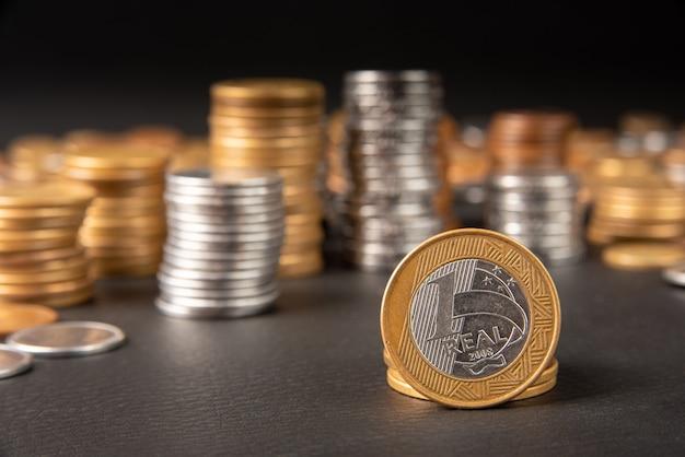 Монеты, бразильские монеты разного количества сложены и одна настоящая монета на переднем плане на черной коже, выборочный фокус.