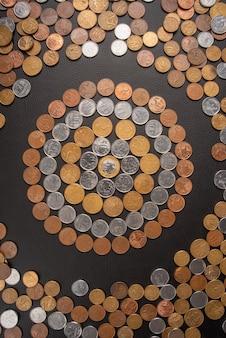 Монеты, бразильские монеты разного достоинства разложены по черной кожаной поверхности, вид сверху.