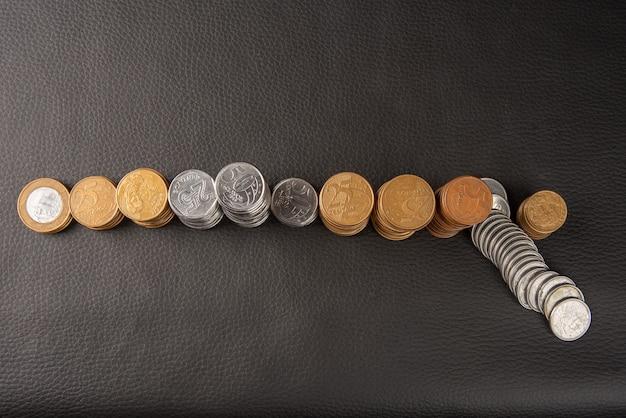 Монеты, бразильские монеты различного достоинства, уложенные на черной коже, выборочный фокус.