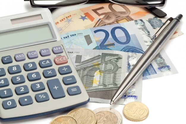 Coins and cash with pen along with glasses and pocket calculator