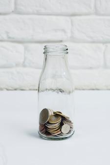 Monete raccolte nella bottiglia di vetro del latte contro il muro bianco
