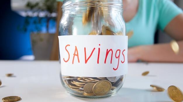 돈을 절약하기 위해 유리 항아리에 떨어지는 동전. 금융 투자, 경제 성장 및 은행 저축의 개념.