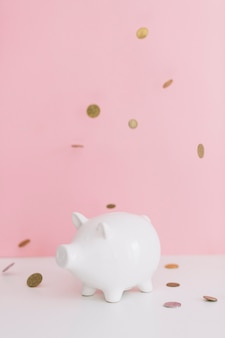 Coins falling over the white piggybank against pink background