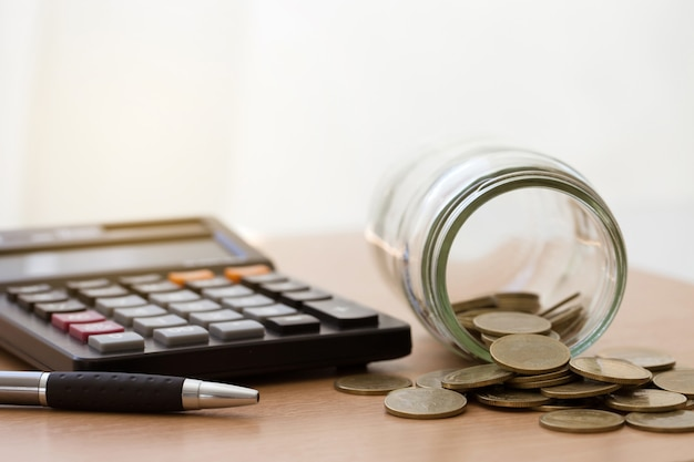 Coins in glass jar and calculator on wooden table.money saving financial concept