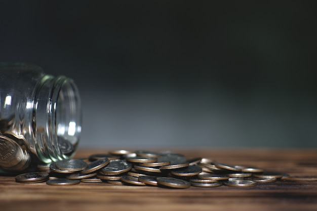 Coins in the glass jar on old wood plank