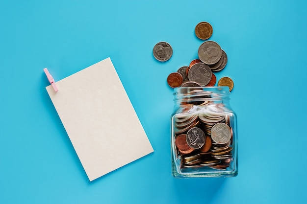Coins in glass jar and outside, thai currency money with blank white paper card