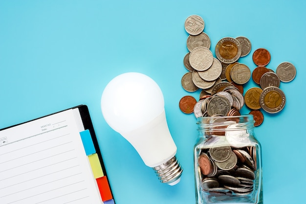 Coins in glass jar and outside with glowing led light bulb and blank notebook on blue back