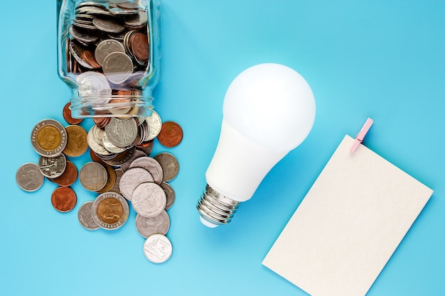 Coins in glass jar and outside with glowing led light bulb and blank paper card on blue ba
