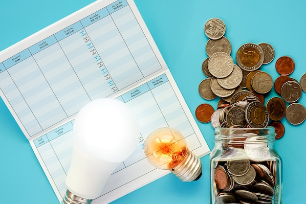 Coins in glass jar and outside with glowing light bulb, led lamp and saving book on blue b