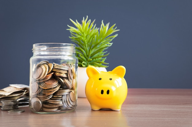 Coins in a glass jar with pig piggy bank