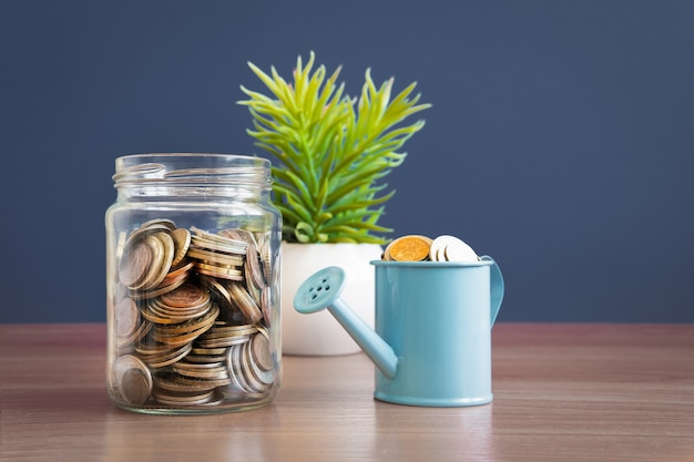 Coins in a glass jar with watering can with money. investment concept. the economic growth. business management. accumulation of capital.