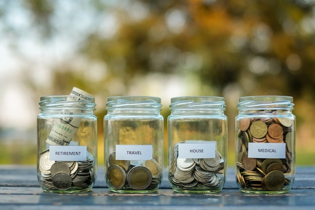 Coins in glass jars, save money for the future concept.