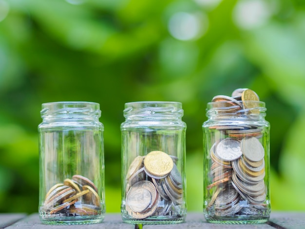 Coins in glass money jar on the wood table. saving money concept.