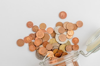 Coins going out from a dropped glass jar, isolated on white