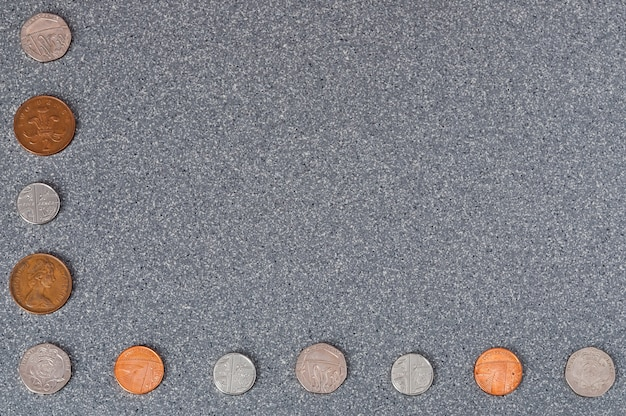 Coins of great britain of different dignity against the background of gray granite.