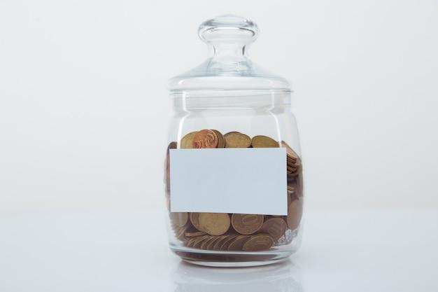 텍스트에 대 한 공간을 가진 유리 은행에 동전. 저축 개념
