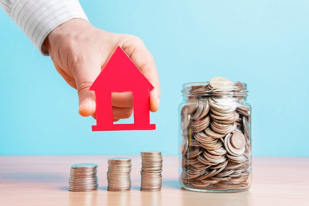 Монеты в стеклянной банке. рука держит дом. инвестиционная концепция. накопление капитала. деньги дома.
