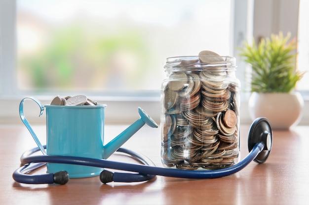 ガラスの瓶の中のコイン。水やりと聴診器。健康保険。投資コンセプト。資本の蓄積。