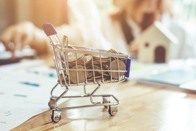 Монеты в корзине на столе. концепция покупок в супермаркете