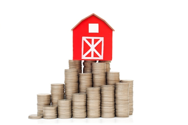 Монеты в стопке для экономии денег и небольшой красный дом концепция роста бизнес-инвестиций