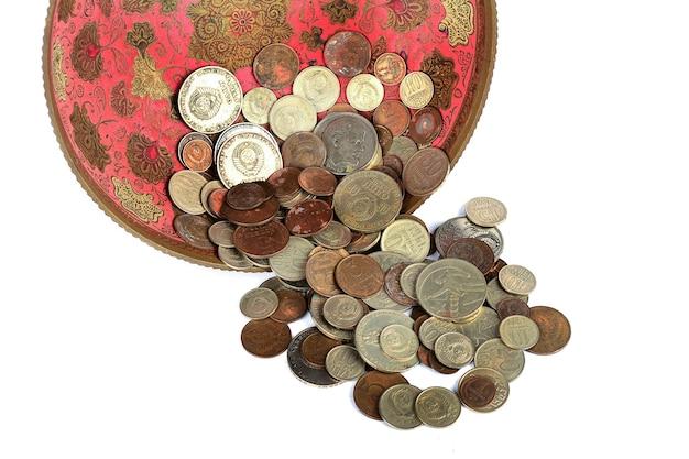 Монеты в древней вазе на белом фоне