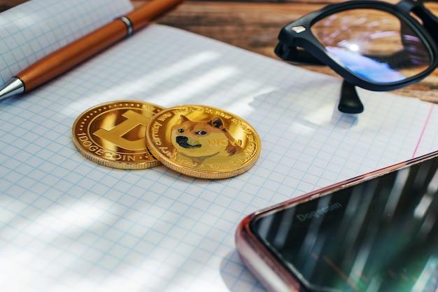 클로즈업된 동전, 노트북 배경에 있는 dogecoin 암호 화폐, 태양 광선