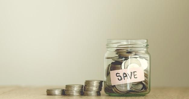 お金を節約する金融の概念のためのガラスの瓶のコイン