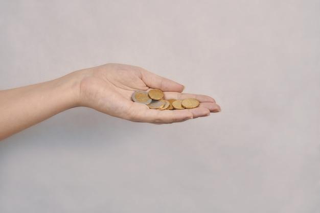 金銭的貯蓄の寄付と施しの金属コインの概念を持つ女性の手にコイン