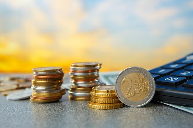 힙에 동전과 일출 배경에 계산기. 높은 비용 개념.