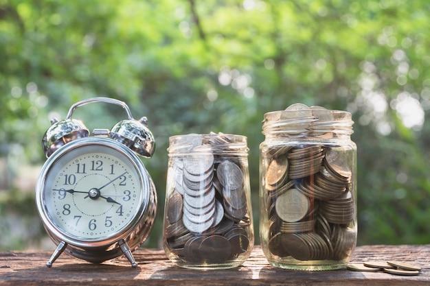 Монеты в банке с будильником на фоне природы, бизнес-концепция концепции