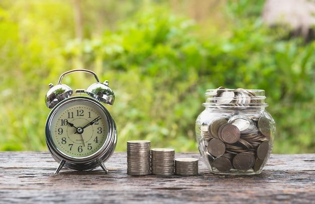 Монеты в банке с деньгами стека растут деньги и будильник