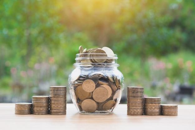 Монеты в банке с деньгами стека растут деньги, концепция финансового бизнеса