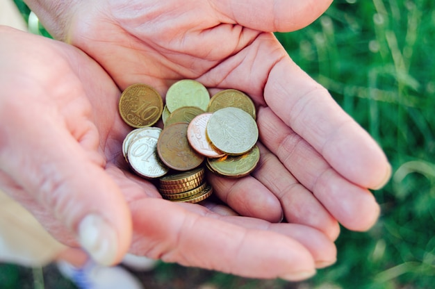 Монеты в старых руках бабушки крупным планом