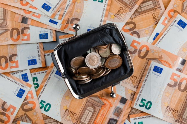 Монеты в кошельке на банкнотах и гипсовом столе.