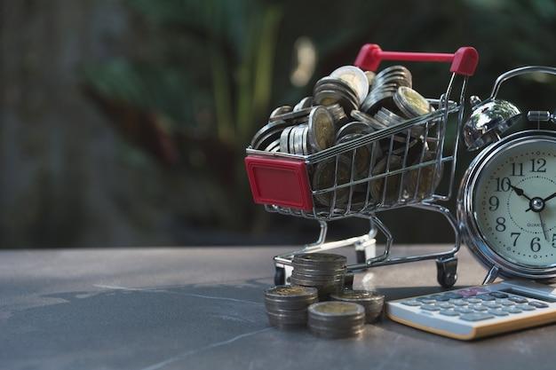 Монеты в корзине с деньгами стека растут деньги и будильник.
