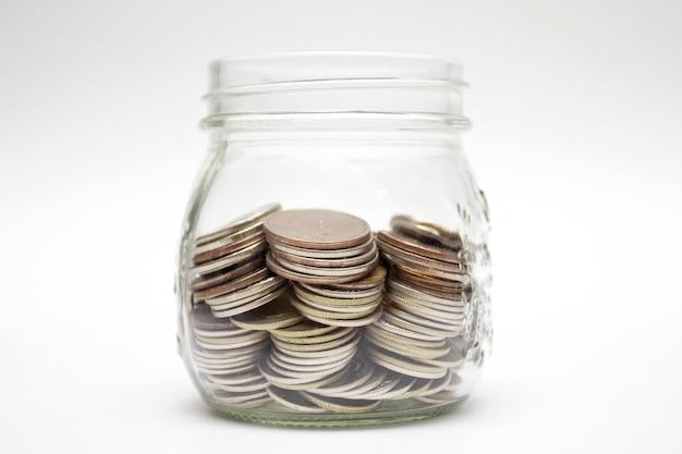 흰색 바탕에 유리 항아리에 동전입니다. 돈 절약 개념입니다.