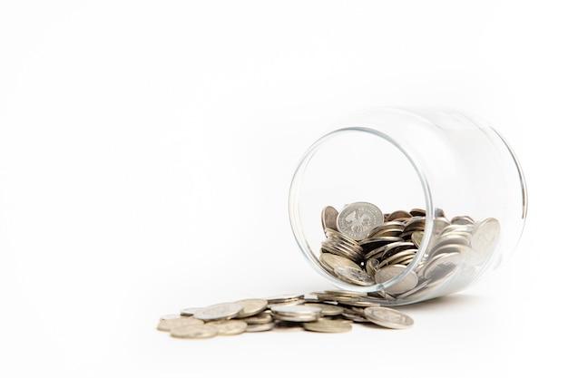 ガラスの瓶の中のコインと白い背景で隔離の周りに散らばっています