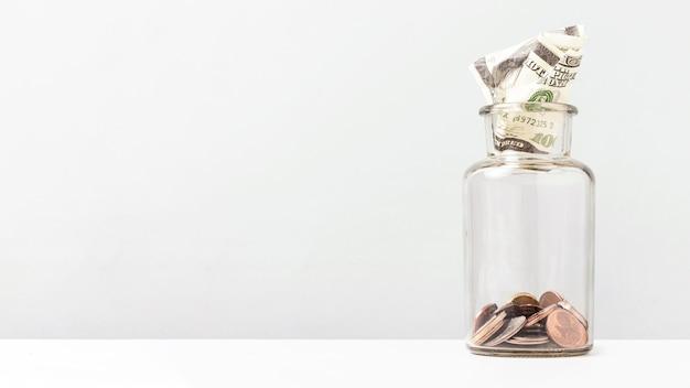 Monete all'interno di una bottiglia con copia spazio