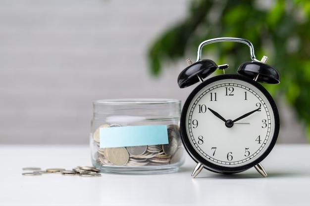 Coins in jar with alarm clock
