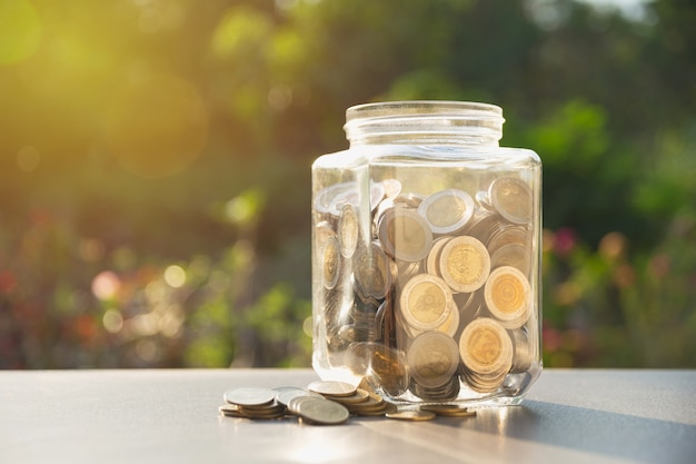 Coins in jar with money stack, concept finance, accounting