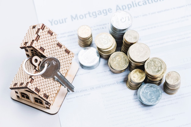 Coins and key on sheet of mortgage application Free Photo