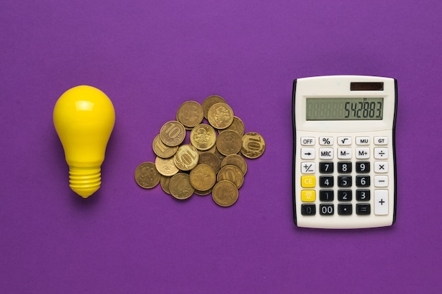 Coins, a light bulb and a calculator on a purple background. the concept of increasing electricity payments.