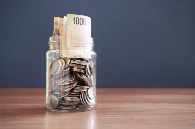Coins and money in a glass jar on a dark background. investment concept. the economic growth. business management. accumulation of capital. copy space.